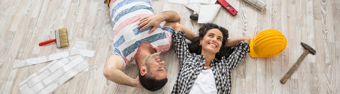 man and woman laying on ground surrounded by construction items.
